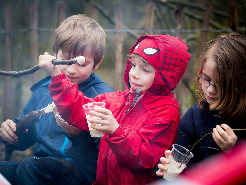 Children roasting marshmallows during an SSG outdoor adventure birthday party in Bedfordshire