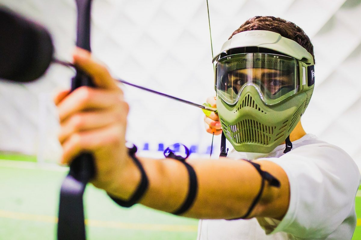 A teenager preparing to shoot an arrow during our archery tag activity birthday party