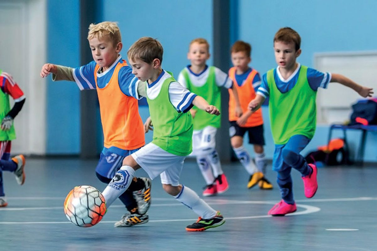Young children playing football during a football fun party hosted by SSG in Bedfordshire